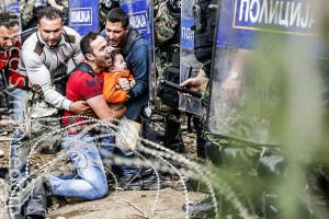 Refugees trapped between Macedonian riot police and razor wire on the Greek border. Image by Freedom House on Flickr, licenced by creative commons.